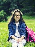 牛仔裤衬衣的美丽的白肤金发的女小学生女孩读书的在与一个背包的草在公园 库存图片