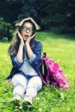 牛仔裤衬衣的美丽的白肤金发的女小学生女孩读书的在与一个背包的草在公园 图库摄影