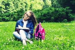 牛仔裤衬衣的美丽的白肤金发的女小学生女孩读书的在与一个背包的草在公园 免版税库存照片