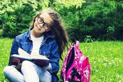 牛仔裤衬衣的美丽的白肤金发的女小学生女孩读书的在与一个背包的草在公园 免版税图库摄影