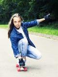 牛仔裤衬衣的美丽的白肤金发的青少年的女孩,在滑板在公园 免版税图库摄影