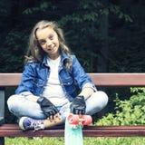 牛仔裤衬衣的美丽的白肤金发的青少年的女孩,坐与背包和滑板的长凳在公园 免版税图库摄影
