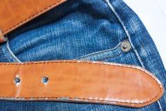 牛仔裤,棕色传送带 库存照片