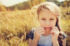 牛仔裤整体使用的愉快的儿童女孩在晴朗的领域 库存图片