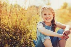 牛仔裤整体使用的愉快的儿童女孩在晴朗的领域 免版税库存照片