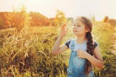 牛仔裤整体使用的愉快的儿童女孩在晴朗的领域 免版税库存图片