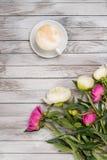 牡丹和咖啡花束在轻的木背景的 顶视图 免版税库存照片