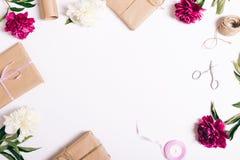 牡丹和礼物的欢乐构成在一张白色桌上 免版税图库摄影