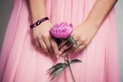 牡丹花在有花边的正式舞会裙子的女性手上 免版税库存图片