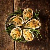 牡蛎盛肉盘与焦干酪顶部的在表上 免版税图库摄影