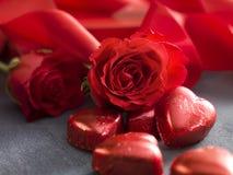 牡鹿塑造了与华伦泰` s天玫瑰和红色丝带的巧克力 免版税库存图片