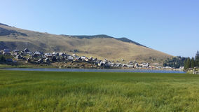 牧人村庄和山湖 库存图片