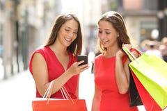 购物与一个巧妙的电话的两个时尚顾客 免版税库存照片