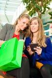 购物与在购物中心的袋子的两名妇女 图库摄影