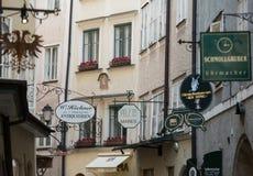 购物与多个广告标志的街道在萨尔茨堡- Getreidegasse Getreidegasse,是其中一条最旧的街道在Salzbur 库存照片
