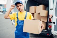 货物交付,与箱子的男性传讯者在手中 免版税库存照片