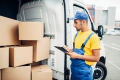 货物交付,与箱子的男性传讯者在手中 免版税库存图片
