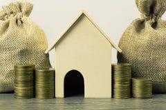物产投资,房屋贷款,房子抵押概念 与堆的一个小屋模型硬币和金钱袋子在木桌上和 免版税库存图片