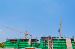 物产有起重机和明白蓝色的建造场所的图象 库存照片