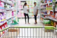 购物台车和迷离超级市场背景篮子  库存图片