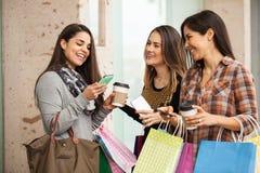 购物和使用他们的智能手机的妇女 免版税图库摄影