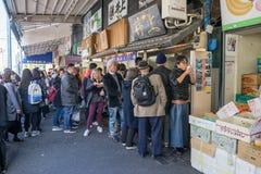 购物和吃一些食物的许多人民在Tsukiji市场上 免版税库存图片