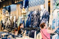购物和浏览在地方衣裳商店的人们 库存图片
