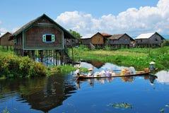物品的运输在一条小船的通过一个浮动村庄 库存照片