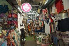 购物在布料商店的游人在Jatujak市场上 免版税图库摄影