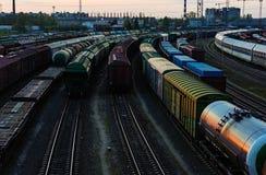 货物在日落的火车平台与有各种各样的物品的容器 库存图片
