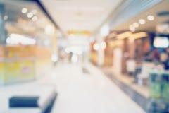 购物在百货商店的人们 Defocused迷离背景 免版税库存照片