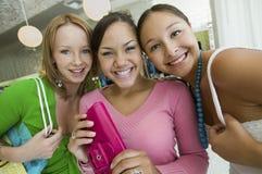 购物在精品店画象的三个女孩 免版税库存图片