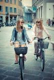 购物在自行车的两名美丽的白肤金发的妇女 图库摄影