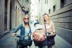 购物在自行车的两名美丽的白肤金发的妇女 免版税库存图片