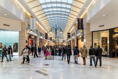 购物在豪华商城的圣诞节的人们 图库摄影