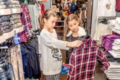 购物在零售店的两个愉快的小女孩 库存照片