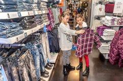 购物在零售店的两个愉快的小女孩 免版税库存图片