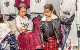 购物在零售店的两个愉快的小女孩 免版税图库摄影