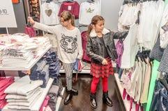 购物在零售店的两个愉快的小女孩 图库摄影