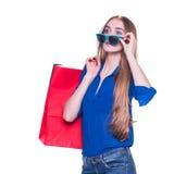购物妇女愉快的微笑的举行的购物袋和退出关于销售 免版税图库摄影