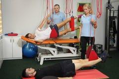 物理疗法:行使在痛苦的生理治疗师治疗监督下在脊椎的用红色绳子设备 免版税图库摄影