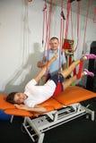 物理疗法:行使在痛苦的生理治疗师治疗监督下在脊椎的用红色绳子设备 图库摄影