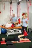 物理疗法:行使在痛苦的生理治疗师治疗监督下在脊椎的用红色绳子设备 免版税库存图片