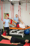 物理疗法:行使在痛苦的生理治疗师治疗监督下在脊椎的用红色绳子设备 库存照片