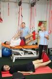 物理疗法:行使在痛苦的生理治疗师治疗监督下在脊椎的用红色绳子设备 免版税库存照片