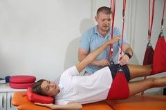 物理疗法:行使在痛苦的生理治疗师治疗监督下在脊椎w的 库存照片