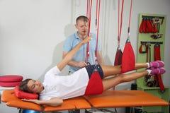 物理疗法:行使在痛苦的生理治疗师治疗监督下在脊椎w的 免版税库存照片