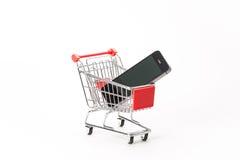 购物的小型运车与智能手机 图库摄影
