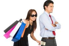 购物的微笑的女性去除的金钱丈夫H 免版税库存照片