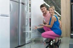 购物美好的年轻的夫妇一个冰箱在超级市场 免版税图库摄影